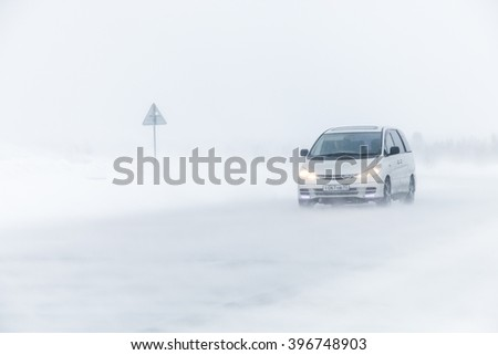 NOVYY URENGOY, RUSSIA - MARCH 20, 2016: Family van Toyota Previa at the interurban freeway during a heavy northern blizzard. - stock photo