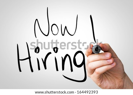 Now Hiring hand writing with a black mark on a transparent board - stock photo