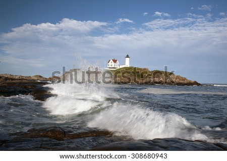 Nubble Light is an island beacon located close to the shore in Maine, surrounded by surf breaking at high tide. - stock photo