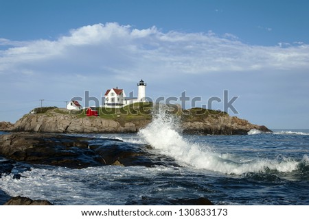 Nubble lighthouse, also referred to as Cape Neddick lighthouse, provides opportunity for great photos of waves crashing over the rocks nearby.  - stock photo