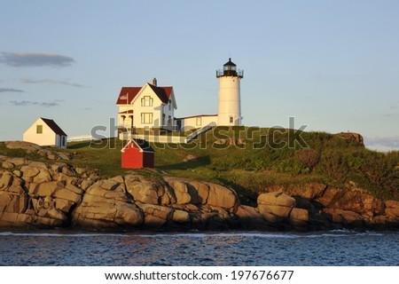 Nubble lighthouse is illuminated as the sun sets. - stock photo