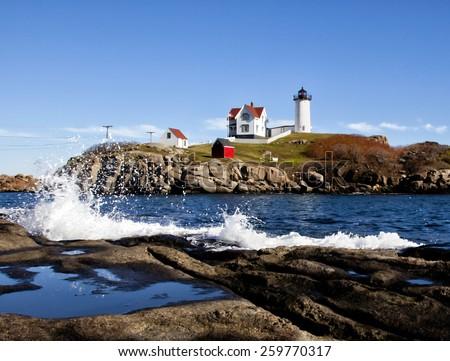 Nubble lighthouse with rough splashing waves - stock photo