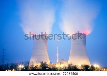 Nuclear power plant blowing huge clouds into dusky sky. - stock photo