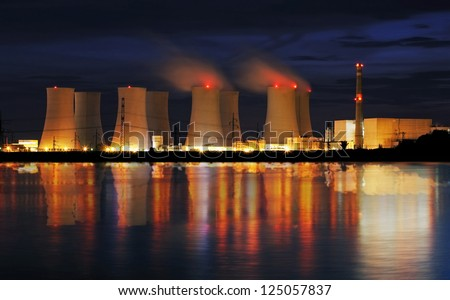 Nuclear power plant by night with reflection - stock photo