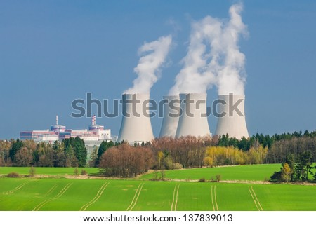 Nuclear Power Plant in Temelin Situated Behind a Green Field (shot on a sunny spring day) - stock photo