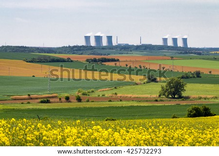 Nuclear power plant on horizon of spring landscape with flowering spring fields. Czech Republic, Europe. - stock photo