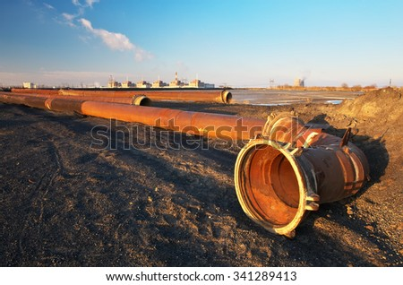 Nuclear power plant units, pipes & coal piles - stock photo