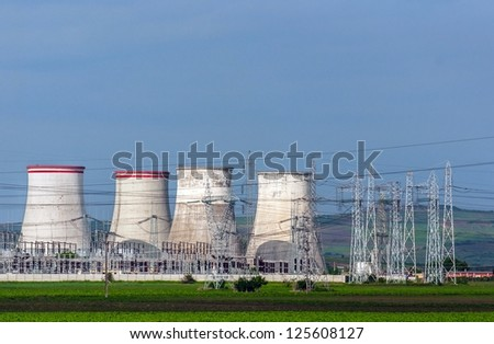 Nuclear power plant with electric pylons and blue sky - stock photo