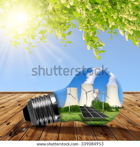 Nuclear power plant with solar panel and wind turbines in lightbulb. Energy resources concept. - stock photo