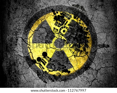 Nuclear radiation symbol painted on cracked ground with vignette with dirty oil footprint over it - stock photo