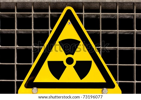 Nuclear radiation warning sign bolted to steel grid - stock photo