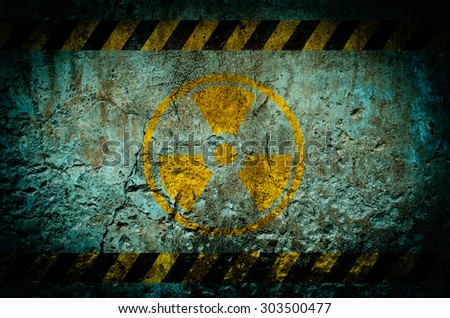 Nuclear radiation warning symbol on dirty wall background with grunge and vignette tone - stock photo