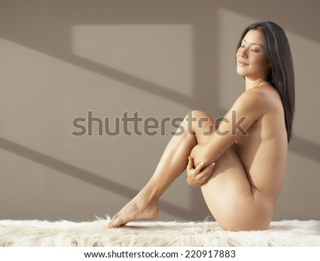 Nude Asian woman pulling knees up to chest - stock photo