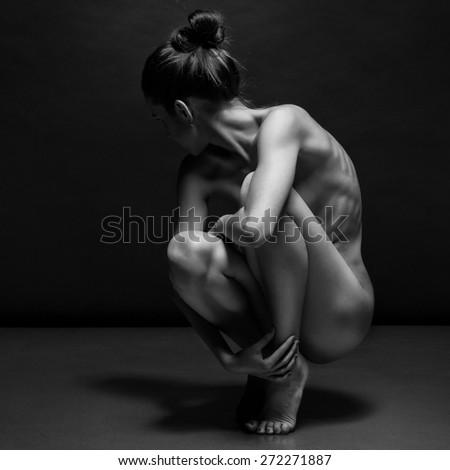 Nude beautiful lady sitting on black background - stock photo