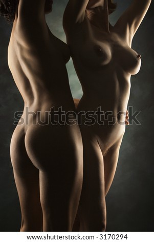 Nude Hispanic and Caucasian women standing together with arms raised over head. - stock photo