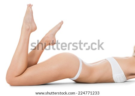 Nude lady in an aesthetic pose sitting on a white background covering her breasts with her arms with her legs raised on tip toe, side view - stock photo