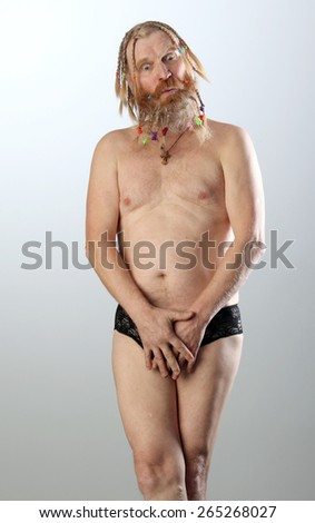 nude portrait full length of an adult male with a beard and mustache, dressed in black briefs studio for light gray background - stock photo