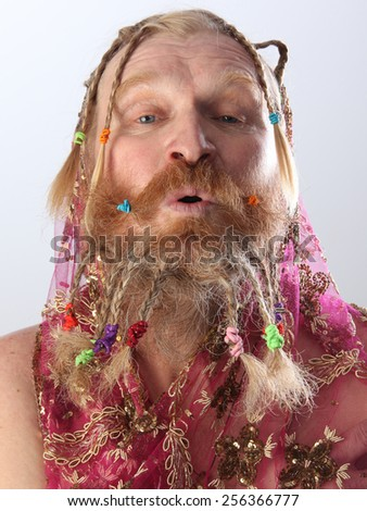 nude portrait of a man with a long beard, mustache and hair braided in pigtails playing with pink translucent scarf studio on light background - stock photo