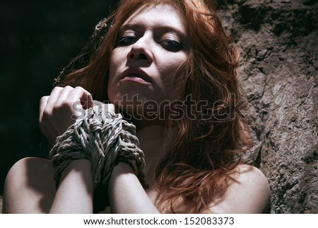 nude redhaired woman bondage in subterranean - stock photo
