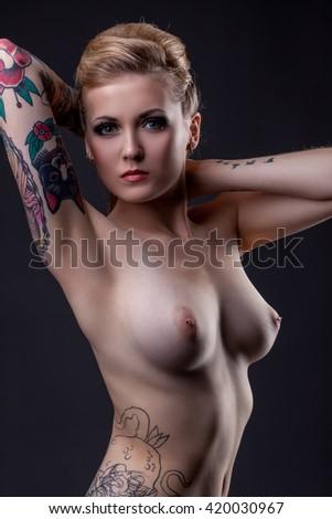 Nude. Studio image of topless tattooed girl poses - stock photo