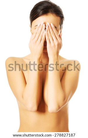 Nude woman covering her eyes because of shame. - stock photo
