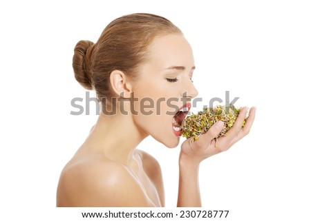 Nude woman eating sunflower sprouts. - stock photo