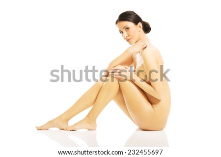 Nude woman sitting with her knees close to the chest holding her shoulder. - stock photo