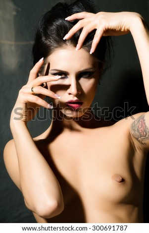 Nude young brunette woman  posing on dark background - stock photo