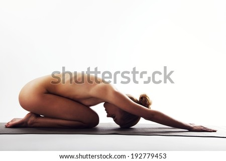 Nude young woman stretching and doing meditation on exercise mat. Caucasian female practicing yoga over white background. - stock photo