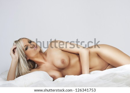 nudes attractive blonde girl relax in bed - stock photo