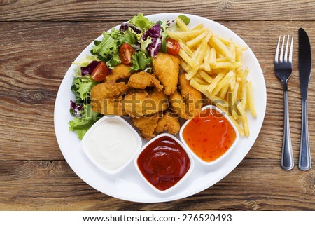 Nuggets and chips on a plate served with dip and salads on a wooden board - stock photo
