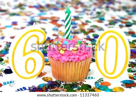 Number 60 celebration cupcake with candle and sprinkles.  Confetti in background. - stock photo