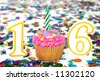 Number 16 celebration cupcake with candle and sprinkles with confetti in background. - stock photo