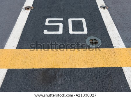 number fifty on white and yellow runway. - stock photo