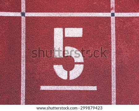 Number five. Big white track number on red rubber racetrack. Gentle textured running racetracks in small athletic stadium. - stock photo