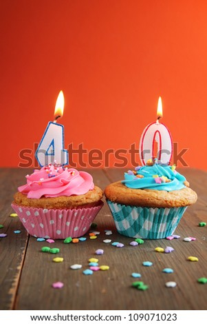 Number forty birthday candles on a pink and blue cupcake on a wooden table - stock photo
