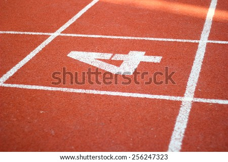 Number four on athletics all weather running track/Number Four On Running Track - stock photo