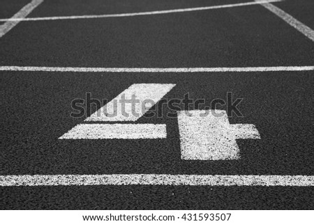 Number four. White track number on red rubber racetrack, texture of racetracks in small stadium. Black and white photo - stock photo