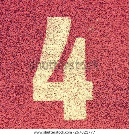 Number four. White track number on red rubber racetrack, texture of running racetracks in small stadium - stock photo