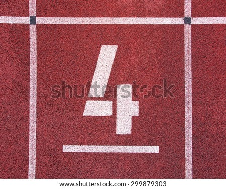 Number four. White track number on red rubber racetrack, texture of running racetracks in stadium - stock photo
