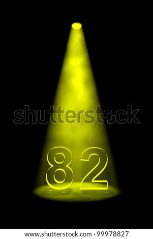 Number 82 illuminated with yellow spotlight on black background - stock photo