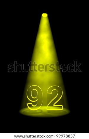 Number 92 illuminated with yellow spotlight on black background - stock photo