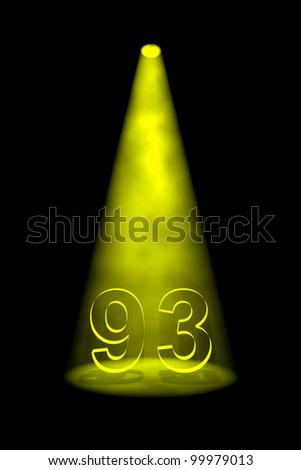 Number 93 illuminated with yellow spotlight on black background - stock photo
