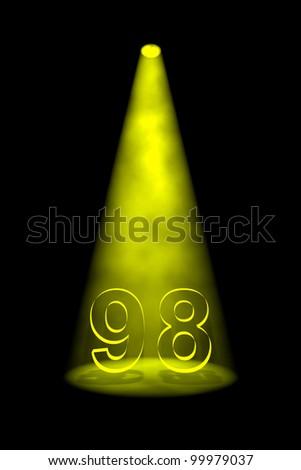 Number 98 illuminated with yellow spotlight on black background - stock photo