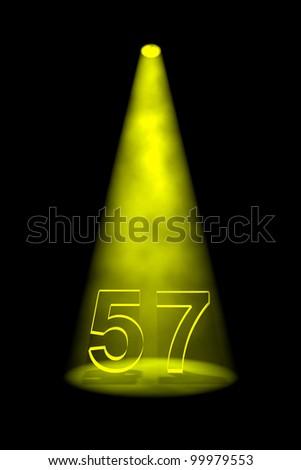 Number 57 illuminated with yellow spotlight on black background - stock photo