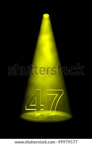 Number 47 illuminated with yellow spotlight on black background - stock photo