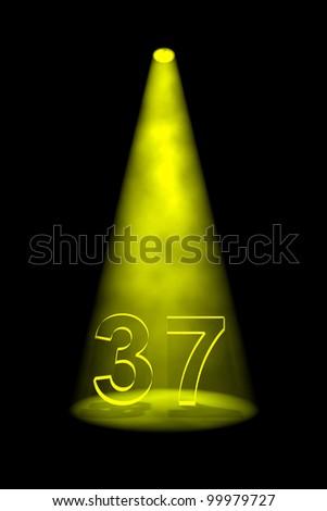 Number 37 illuminated with yellow spotlight on black background - stock photo