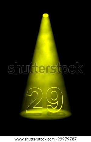 Number 29 illuminated with yellow spotlight on black background - stock photo