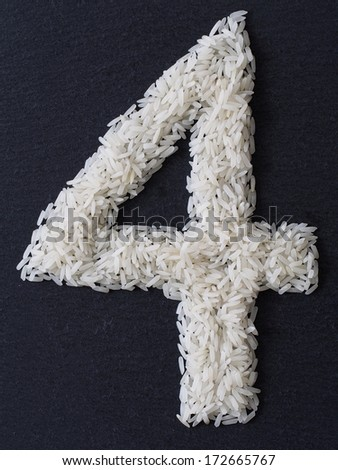 Number 4 made of rice on a black slate - stock photo