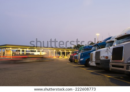 Number of semi trucks of various models and colors in the future on the night truck stop with a lit gas station and blurred lights of a passing semi truck and reflection of the lights on the big rigs. - stock photo